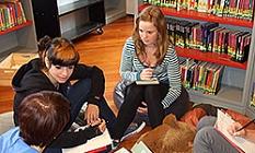 Vier Schülerinnen sitzen in einem Kreis auf Sitzkissen, vor sich Papier und Stifte, um an Aufgaben zu arbeiten.©Universitätsstadt Marburg