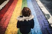 Ein Mädchen oder eine junge Frau kniet auf einem Bahnsteig, auf dem ein Regenbogen gemalt ist.