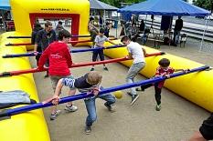 Aktion am Riesenkicker, die Spieler halten sich an ihren Stangen fest und kämpfen um den Ball, die gelbe Umrandung (ähnlich einer Hüpfburg) verhindert Verletzungen und das Wegrollen des Balles. Außerdem sind auf der Umrandung die Stangen befestigt. Auch d©Stadt Marburg