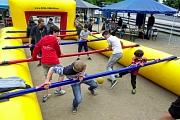 Aktion am Riesenkicker, die Spieler halten sich an ihren Stangen fest und kämpfen um den Ball, die gelbe Umrandung (ähnlich einer Hüpfburg) verhindert Verletzungen und das Wegrollen des Balles. Außerdem sind auf der Umrandung die Stangen befestigt. Auch d