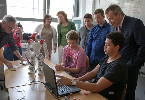 """Algorithmisches Denken erforderlich: Oberbürgermeister Dr. Thomas Spies (rechts) lässt sich von einer Arbeitsgruppe des Robotikums erklären, wie sie """"Nao"""" dazu bringen, auf einen Befehl zu reagieren.©Stadt Marburg, Patricia Grähling"""
