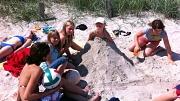 Mehrere Jugendliche haben jemanden in einer Sandburg eingegraben, aber keine Sorge, sie lächelt noch.