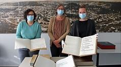 Sandra Baumgarten, Leiterin des Stadtarchivs, präsentiert gemeinsam mit ihren Mitarbeiterinnen Stina Dörr (l.) und Nadine Englert die historischen Bände des Goldenen Buches der Stadt Marburg, die im Stadtarchiv eingesehen werden können.