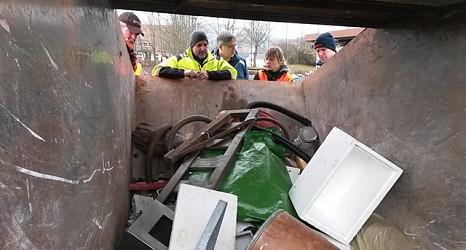 Das Foto zeigt Aktive des Sauberhaften Frühjahrsputz in Elnhausen wie sie in die gefüllte Abfallmulde schauen.©DBM
