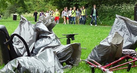 Das Foto zeigt Abfallsäcke und einen Fahrradrahmen ohne Reifen im Vordergrund. Dahinter gehen Kinder in Warnwesten mit Papierzangen und sammeln Abfälle ein.©DBM, Sonja Stender