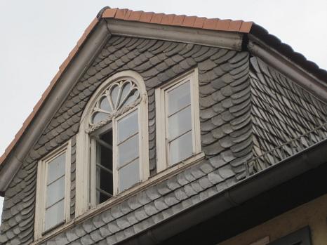 Fassade mit losen Schieferplatten und Spalten unter dem Dach. Hier könnten Fledermäuse sein.