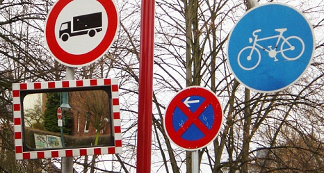 Das Foto zeigt verschiedene Verkehrsschilder und einen Spiegel an einem Mast.©DBM, Sonja Stender