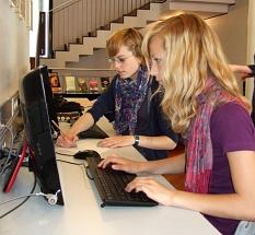 Zwei Schülerinnen recherchieren an den PC-Arbeitsplätzen im Medienbestand der Stadtbücherei.