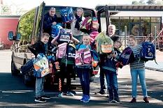 Kinder und Erwachsener präsentieren stolz den mit Schulranzen voll geladenen Bus.©Universitätsstadt Marburg