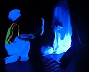 2 Figuren vom Schwarzlicht leuchtend in Farbe gesetzt.