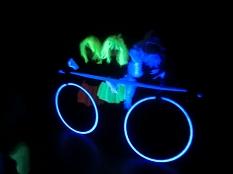 """Ein """"leuchtendes Fahrrad"""" aus fluorisierenden Gegenständen unter Schwarzlicht.©Universitätsstadt Marburg"""