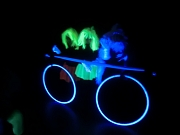 """Ein """"leuchtendes Fahrrad"""" aus fluorisierenden Gegenständen unter Schwarzlicht."""