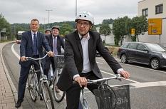 Oberbürgermeister Dr. Thomas Spies (von links), Bürgermeister Wieland Stötzel und Stefan Eckert, Leiter der Siemens-Division Mobility in Süddeutschland, testen gemeinsam die Sitraffic SiBike-App in Marburg.©Stadt Marburg, Patricia Grähling