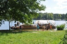 Ein Boot, mindestens 10 m lang, mit Dach liegt am Ufer, einige Jugendliche scheinen ab- oder zu zusteigen.©Universitätsstadt Marburg