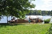 Ein Boot, mindestens 10 m lang, mit Dach liegt am Ufer, einige Jugendliche scheinen ab- oder zu zusteigen.