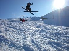 Ein Skifahrer macht einen großen Sprung, alles ist schneebedeckt, vor blauem Himmel scheint die Sonne.©Stadt Marburg