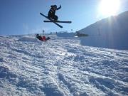 Ein Skifahrer macht einen großen Sprung, alles ist schneebedeckt, vor blauem Himmel scheint die Sonne.