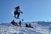 2 Leute sehen gebannt einem Skifahrer hinterher, der im tollkühnen Flug an ihnen vorüber zieht.