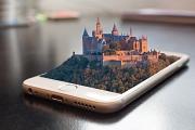Ein Smartphone liegt auf dem Rücken, aus dem Display ragt ein Schloss heraus - es muss sich hier um eine digitale Trickserei handeln ;-)