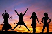 4 Mädchen stehen vor einem Sonnenuntergang, man erkennt nur die Schattenumrisse. Außerdem sieht man einige Vögel.