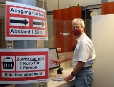 Stadtbüchereileiter Jürgen Holzer weist darauf hin, dass das Tragen eines Mund- und Nasenschutzes Pflicht ist.©Thomas Steinforth, Stadt Marburg