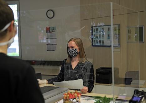 Alle Schalter für den Publikumsverkehr im Stadtbüro sind mit einer Plexiglasscheibe ausgestattet, die Mitarbeiter*innen wie Paulina Pape ebenso wie die Kund*innen schützen.©Birgit Heimrich, Stadt Marburg