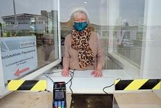 Claudia Herklotz vom Stadtbüro bedient am großen Fenster neben dem Haupteingang Bürger*innen, die Dokumente beantragen oder abholen möchten, ohne das Gebäude zu betreten. Das Fenster ist ebenso wie das daneben zusätzlich mit Plexiglas ausgestattet.©Birgit Heimrich, Stadt Marburg