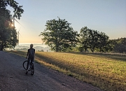 Radfahrer im Feld vor Windrad