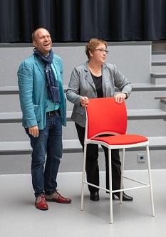 Stadträtin Kirsten Dinnebier übergibt Schulleiter Thomas C. Ferber einen Stuhl – stellvertretend für die neue Bestuhlung im Pausenbereich des Forums.©Patricia Grähling, Stadt Marburg
