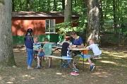 Ein Betreuer und mehrere Kinder basteln unter schattigen Bäumen an einem Tisch.