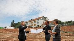 OB Spies (li.) mit Kai Heyd und Stefanie Kempf vom Bauamt bei einer Ortsbegehung: Von einem Holzdeck des fertigen Familienzentrums wird man später Ziegen auf der Böschung beobachten können.