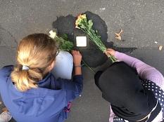 2 Jugendliche legen Blumen zu einem neu gesetzten Stolperstein.©Universitätsstadt Marburg