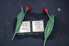 2 Stolpersteine zum Gedenken an die Verbrechen der NS-Zeit, links und rechts daneben jewils eine rote Tulpe.©Universitätsstadt Marburg