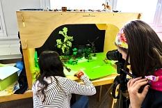 1 Mädchen stellt in einer sogenannten Trickbox eine Szene auf, im Vordergrund ein anderes Mädchen an einer Kamera auf einem Stativ.©Universitätsstadt Marburg