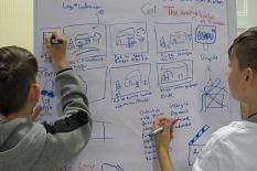 Storyboard - 2 Jungen schreiben an eine Flichart den geplanten Verlauf einer Filmszene.©Universitätsstadt Marburg