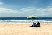 Zwei Menschen auf Liegestühlen unter dem Sonnerschirm am Strand mit Blick aufs Meer.
