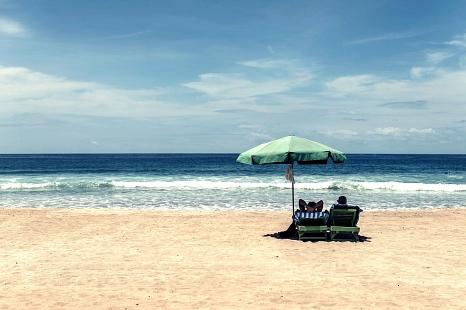 Zwei Menschen auf Liegestühlen unter dem Sonnerschirm am Strand mit Blick aufs Meer.©Pixabay: Free-Photos