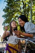 Zwei Mädchen halten ihre Fahrräder und unterhalten sich.
