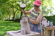 Teilnehmerin im Kurs Steinbildhauerei 2019 bearbeitet Setin drauße unter Bäumen mit Sonnenhut
