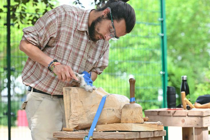 Teilnemer im Kurs Holzbildhauerei bearbeitet ein Stück Holz©Georg Kronenberg