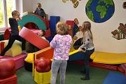 Mit großen, bunten Schaumstoffelementen spielen einige Mädchen und Jungen.