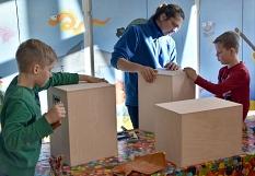 Kinder und Betreuer bauen Trommeln, sogenannte Cajons. Sie sind quaderförmig und aus Holz.©Universitätsstadt Marburg