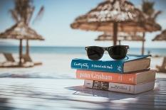 Im Vordergrund liegen Bücher und eine Sonnenbrille, im Hintergrund sind Palmen, Hütten und das Meer zu sehen.©Pixabay