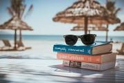 Im Vordergrund liegen Bücher und eine Sonnenbrille, im Hintergrund sind Palmen, Hütten und das Meer zu sehen.