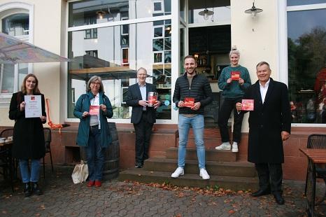 """V. r.: Oberbürgermeister Dr. Thomas Spies, Johanna Krüger (Café """"Frau Friedrich""""), Philip Groß (Inhaber """"Café Großartig""""), Hans-Werner Biehn (Mitinitiator), Susanne Hofmann (Leiterin """"Gesunde Stadt""""), und Lorena Braun (Gesunde Stadt) starten das Projekt """"©Beatrix Achinger, i.A.d. Stadt Marburg"""