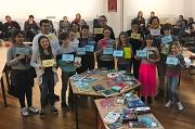 Die Teilnehmer*innen und Organisator*inen auf einem Gruppenbild, vor ihnen Tische mit zahlreichen Büchern.