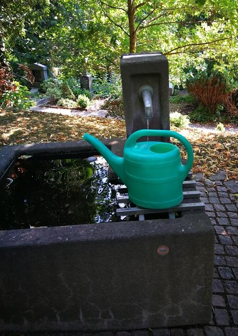 Wasserbecken auf einem Marburger Friedhof mit einer lila Gießkanne©Universitätsstadt Marburg