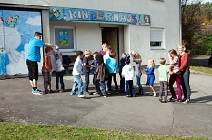 Vor dem Kinderhaus mit dem blau gestalteten Eingang stehen zahlreiche Kinder und warten scheinbar darauf, dass die Gruppe endlich loszieht.©Stadt Marburg