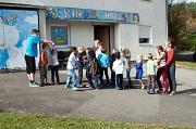 Vor dem Kinderhaus mit dem blau gestalteten Eingang stehen zahlreiche Kinder und warten scheinbar darauf, dass die Gruppe endlich loszieht.