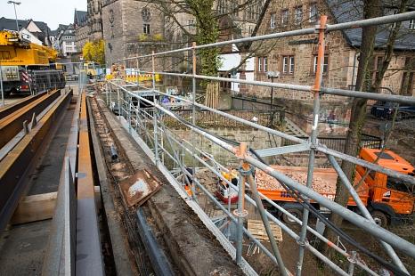 Neben dem Traggerüst im ersten Pfeiler steht nun auch ein Arbeitsgerüst. Von dort aus können die Steinmetze gut gesichert die beschädigten Sandsteine aus der Brücke herausschneiden.©Stadt Marburg, Patricia Grähling